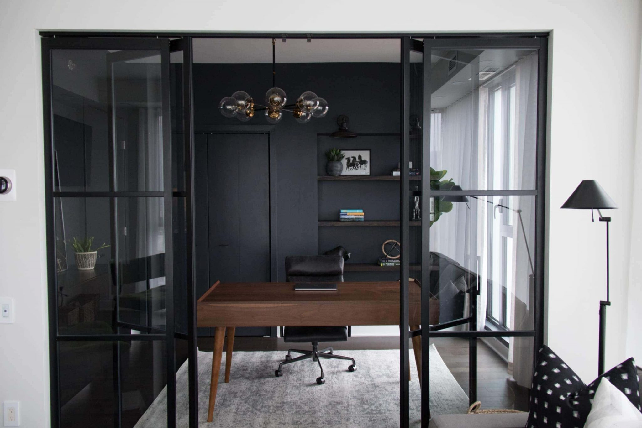 Dark, modern office with a beautiful small chandelier