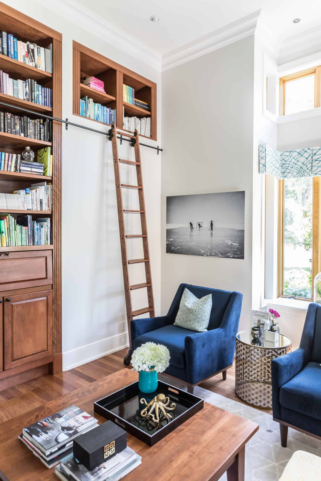 Tall living room with a ladder to reach the top of bookshelves