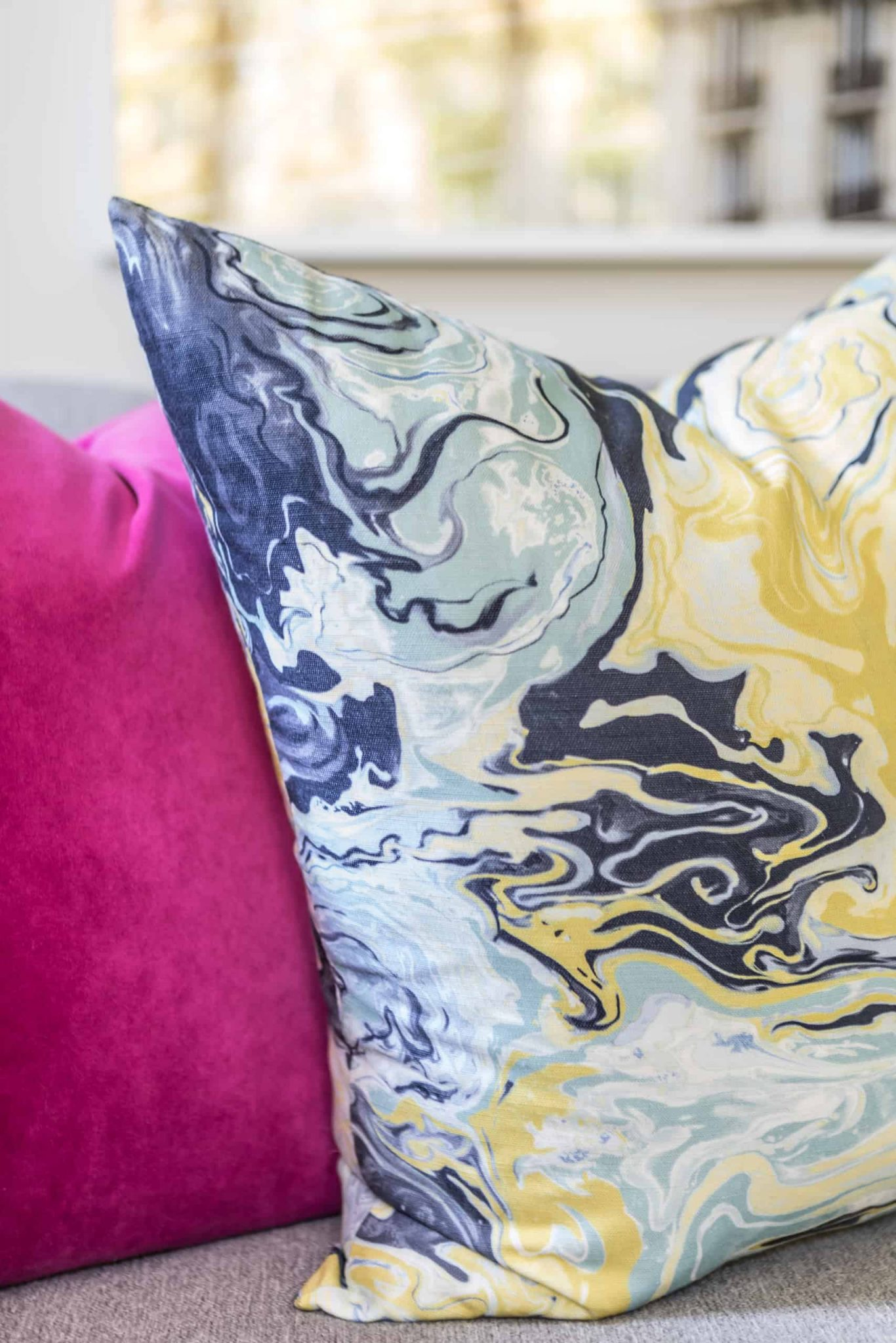 Colorful patterned pillow next to a pink pillow