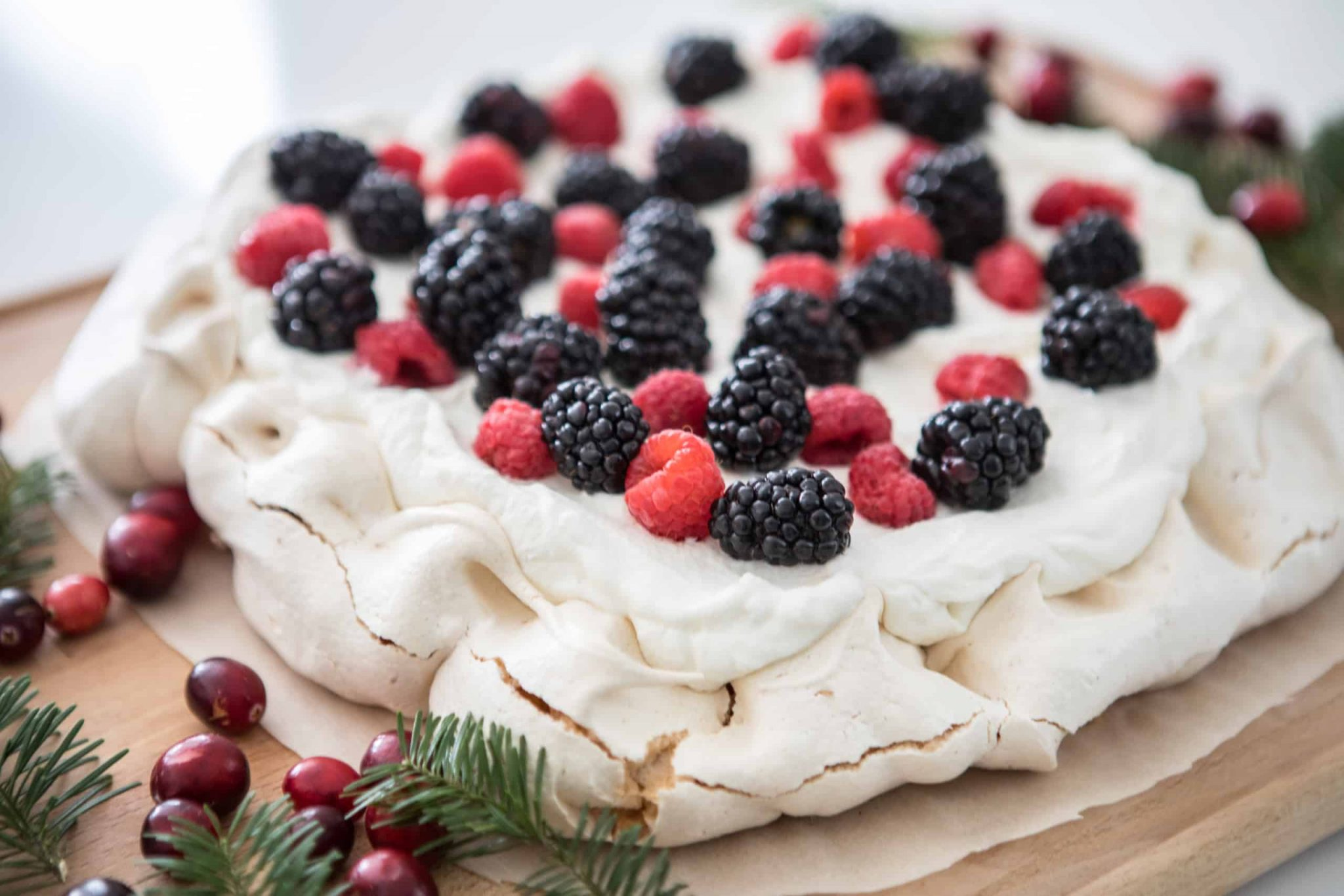 Razzberries and blackberry cake on a wooden plate