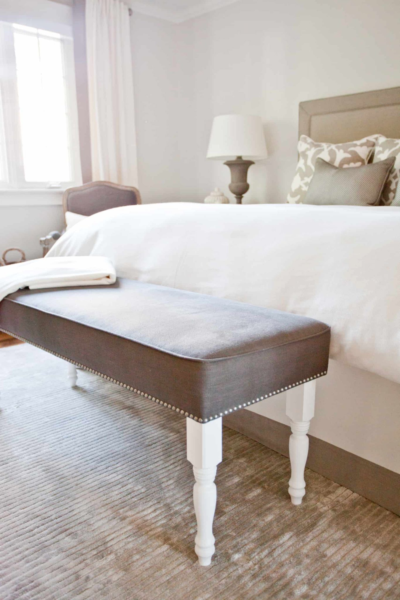 Modern, brown bench against a large bed