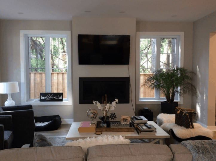 Dark living room with a television above the fireplace