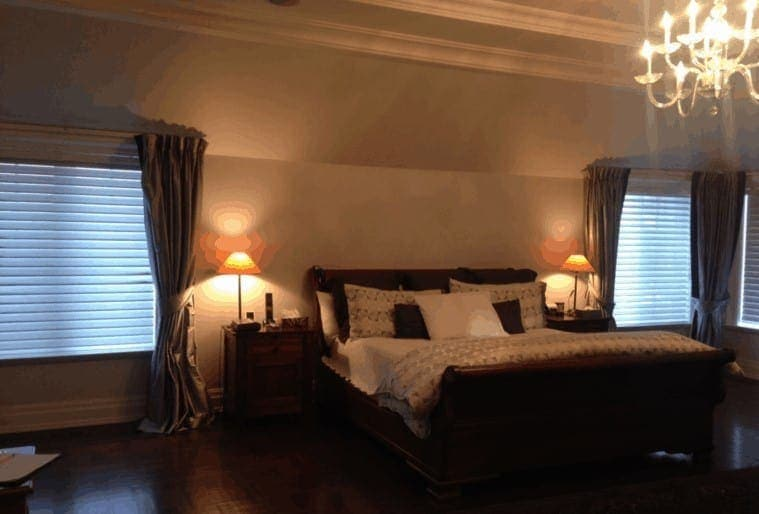 Dark master bedroom with the lamps on