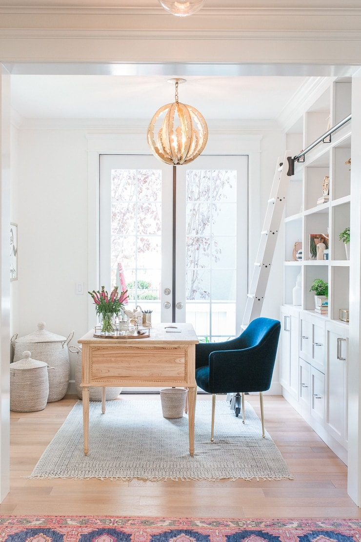 Bright office space containing a round chandelier