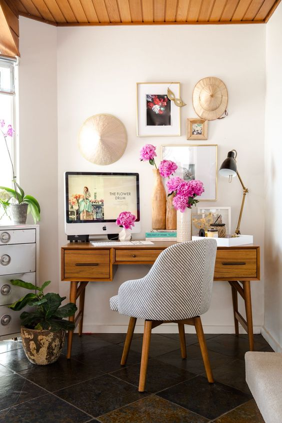 Small, cozy office containing pink flowers