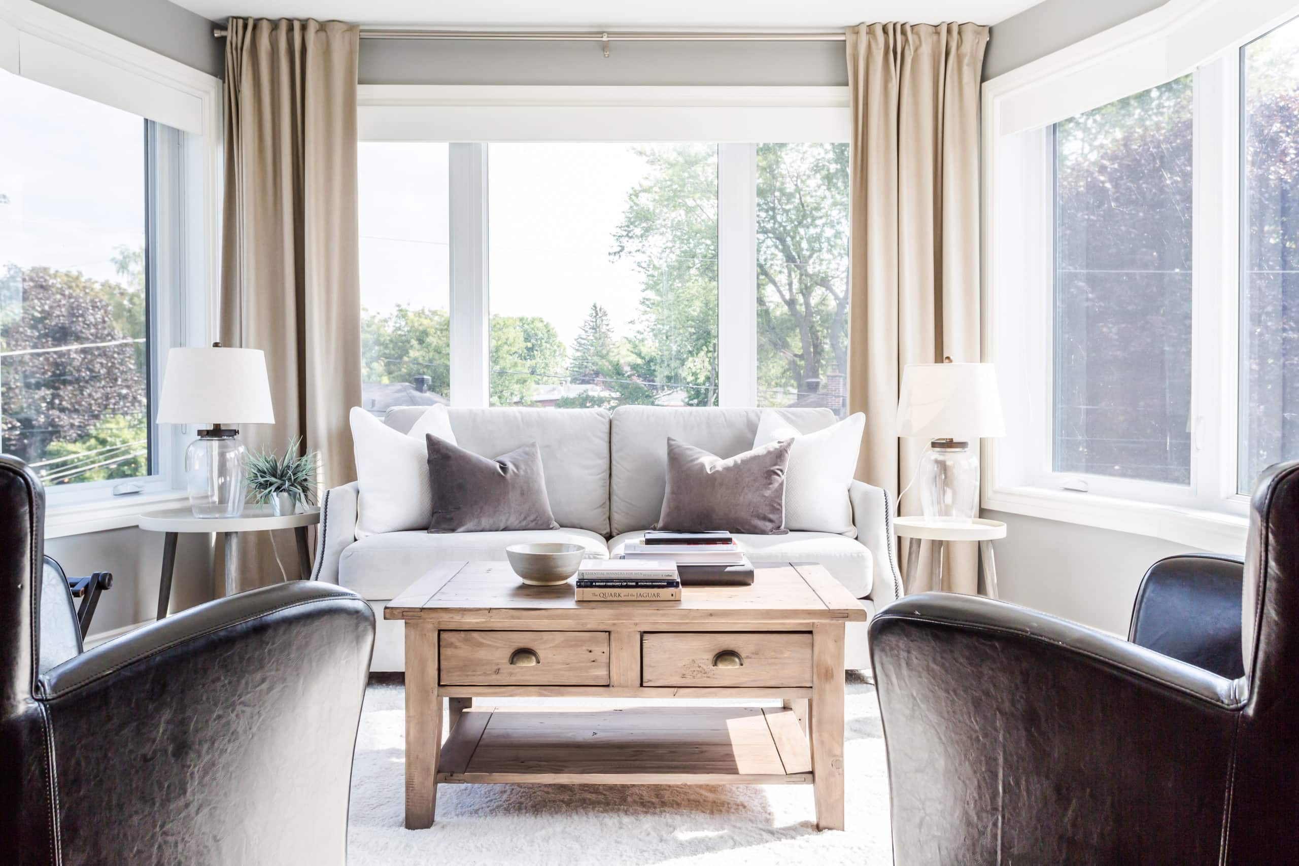 Bright sitting area with three windows revealing a beautiful view