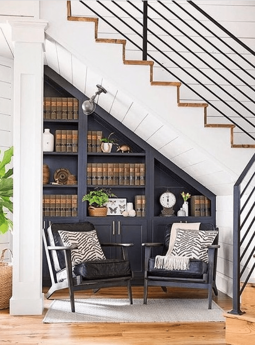 Cozy sitting area underneath the staircase with a built-in bookshelf.