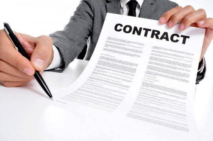 person holding labor contract and pen