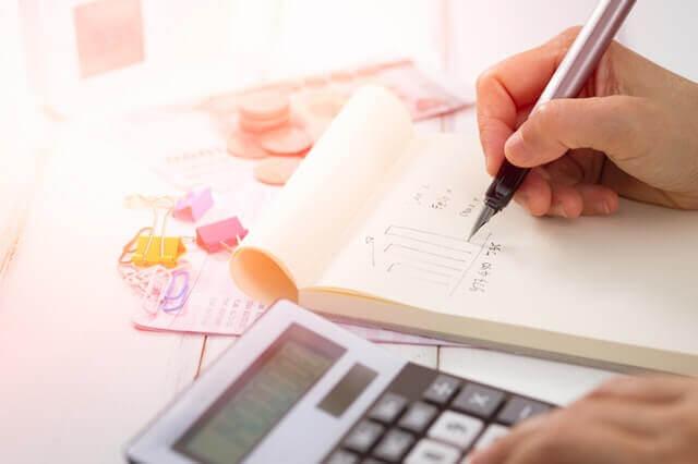 Persona que usa una calculadora, que representa a una persona que calcula los impuestos involucrados en un proceso de formación de LLC en Uruguay.