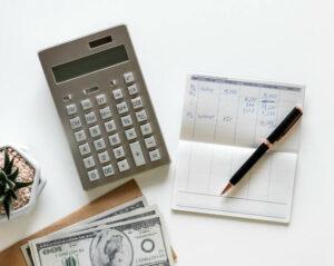 Calculator, book and pen on desk