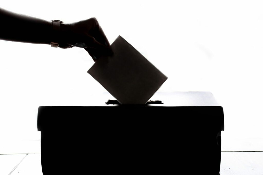 A person casting a vote into the ballot box during elections.