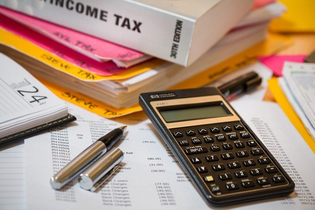 Libro de impuestos sobre la renta sentado en una carpeta con calculadora y bolígrafo, representando los impuestos involucrados cuando un inversionista extranjero registra una sucursal en Guatemala.