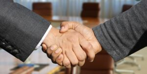 Two persons shaking hands about a trade agreement in Bolivia.