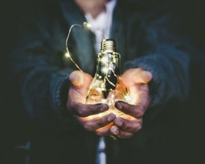 Man holding light bulb in his hands.