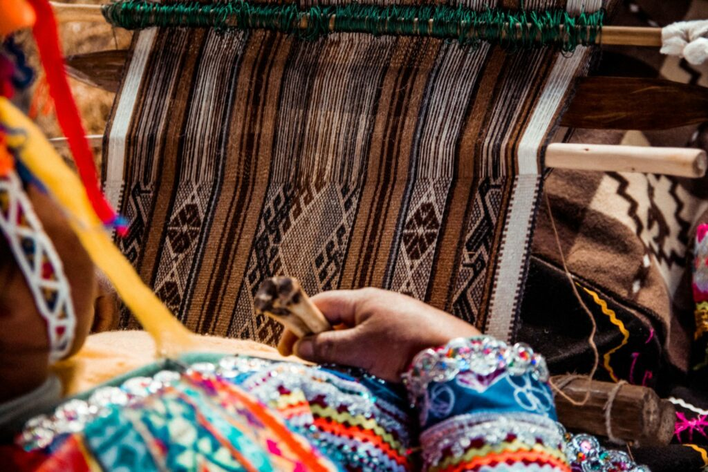 A woman weaving fabric for an NGO in Peru