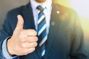Man in business suit giving thumbs up