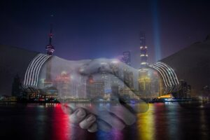 Image of shaking hands superimposed on top of a city at night
