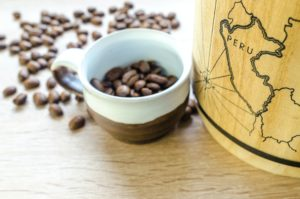 Cup of coffee beans next to map of Peru