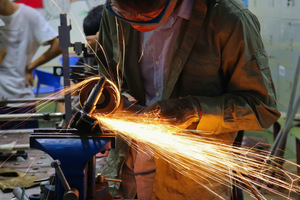 A person welding metal in Mexico's manufacturing sector