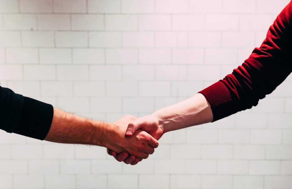 two people shaking hands for business representatives in Brazil.