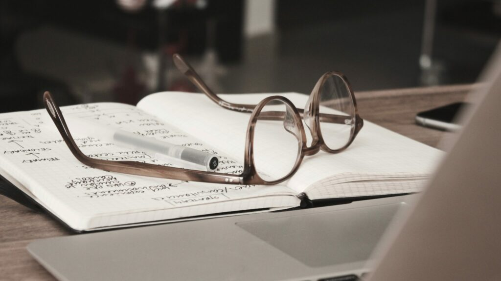 Glasses on top of a notebook.