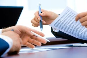 Two people signing a contract