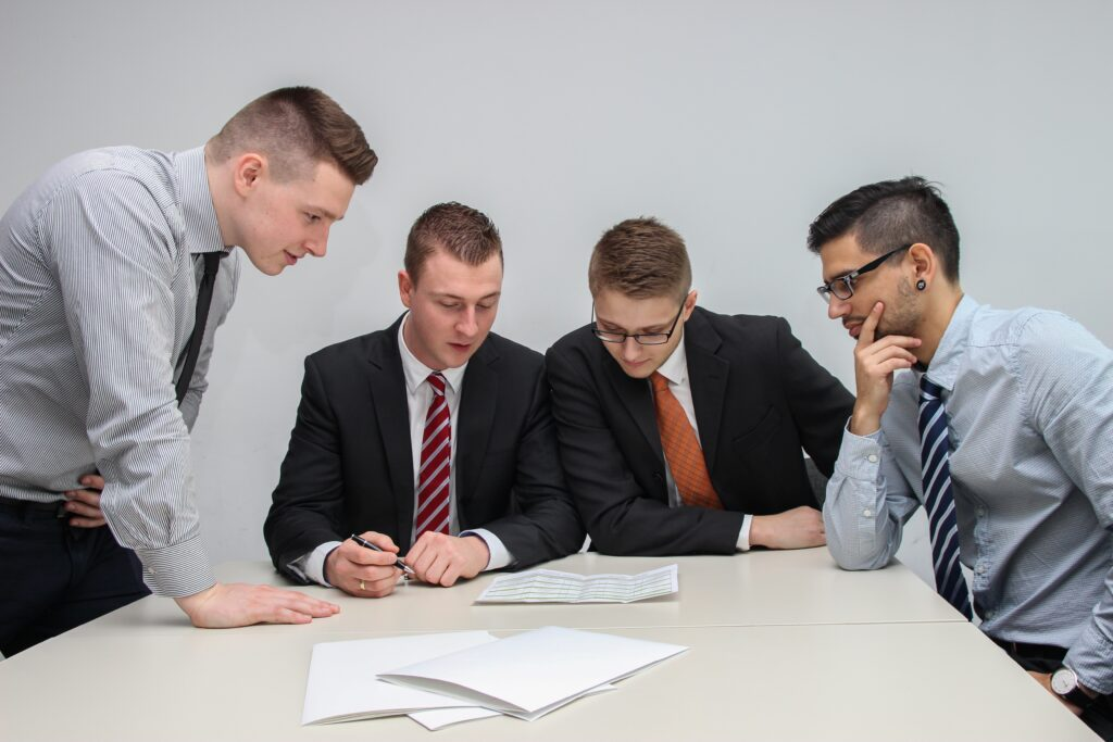 Group of people around a desk looking at paperwork