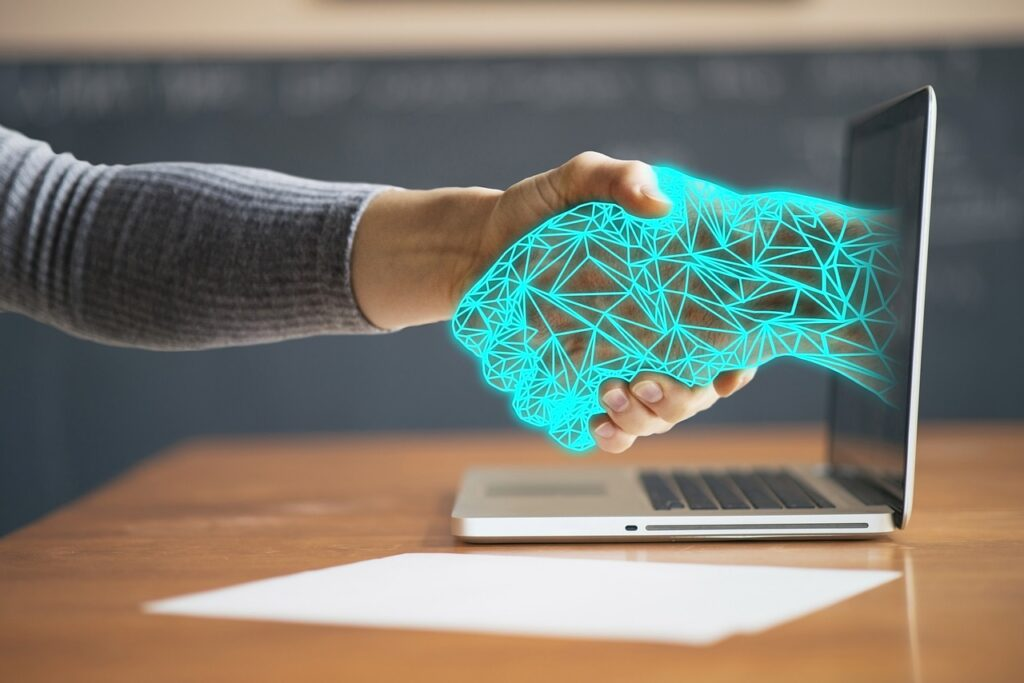 Man shaking hands with a virtual hand coming out of computer screen