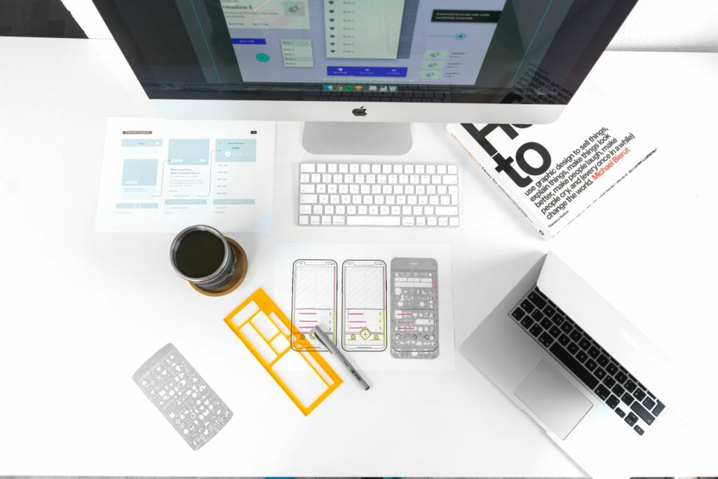Desk showing graphic design book and drawings of a phone