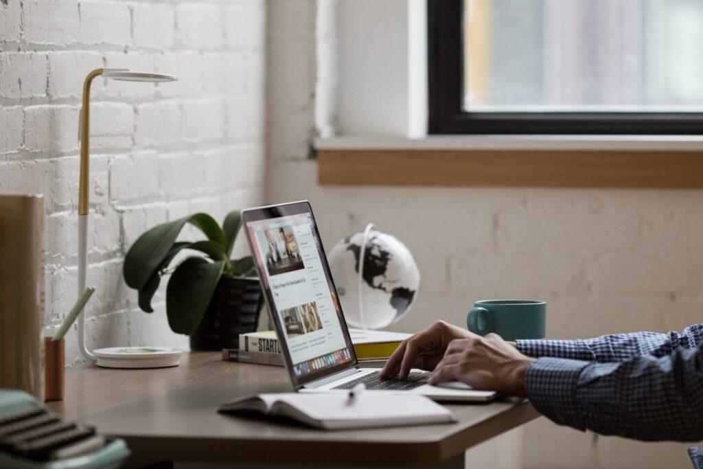 Homem em seu escritório procurando informações em seu computador sobre serviços de Secretariado Corporativo na Bolívia.