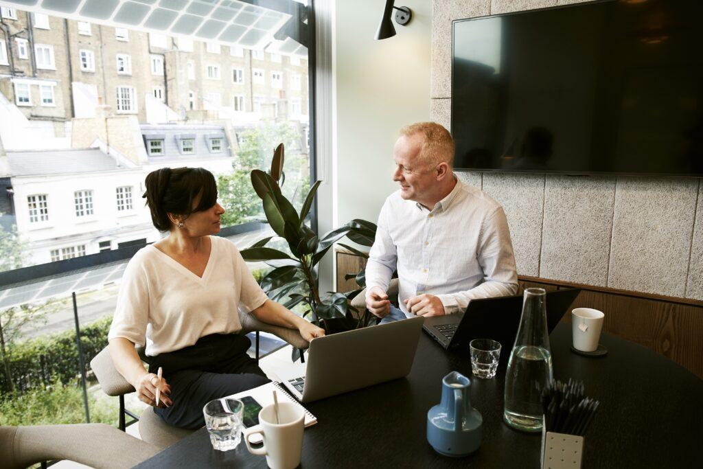Dos personas en una oficina discutiendo sobre los pasos clave para iniciar un negocio en Brasil.