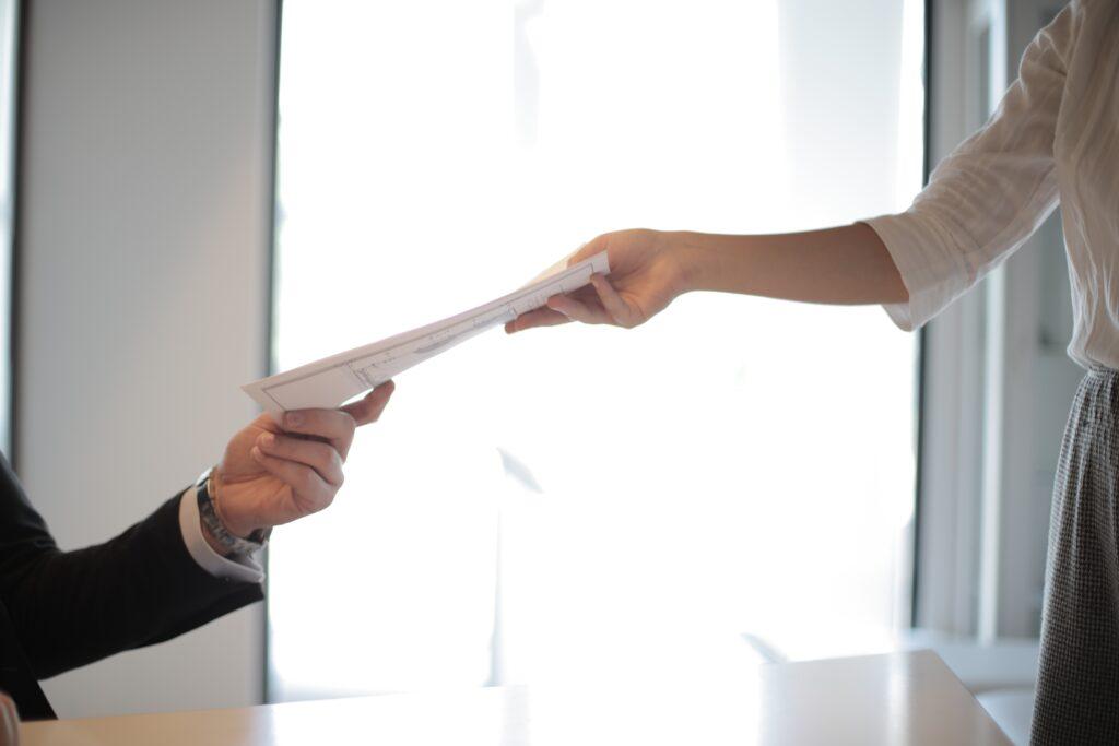 Mujer entregando a un hombre un documento sobre los requisitos de facturación para una empresa extranjera en Paraguay