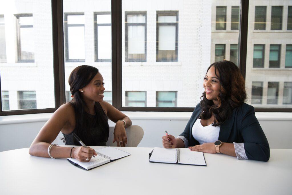 Dos mujeres en una oficina discutiendo sobre cómo trabajar con una OPE en Bolivia.