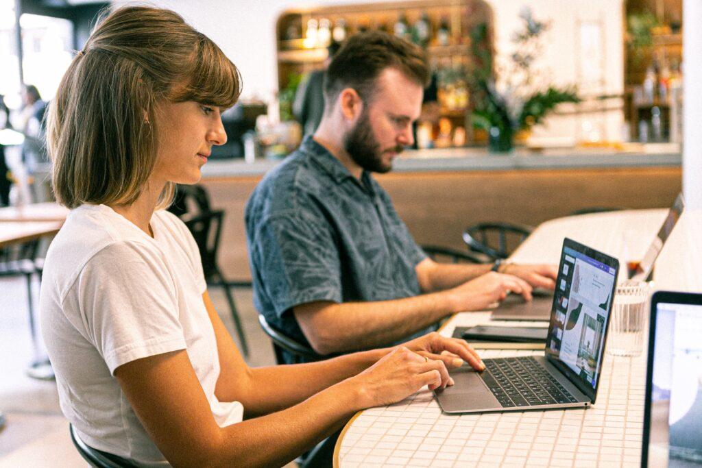Un hombre y una mujer usan sus computadoras para buscar información sobre las startups de Brasil para ver en 2021.