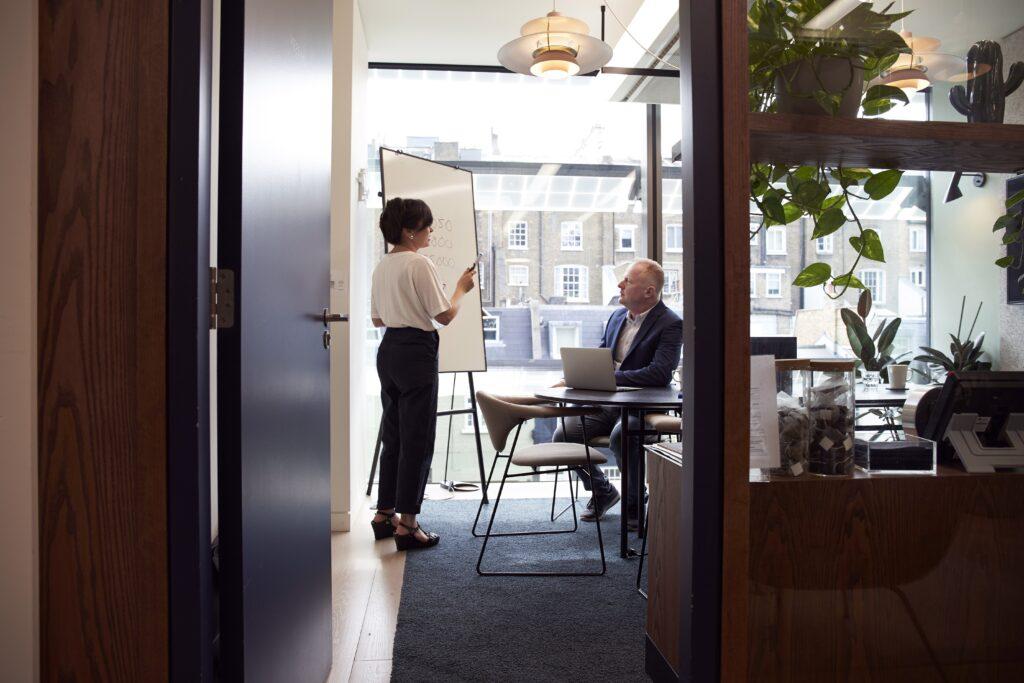 un empresario y una empresaria en una oficina discuten sobre las ventajas de contratar un asesor legal corporativo en Colombia.