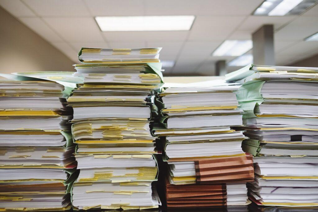 Una pila de papeleo que representa la gran cantidad de registros necesarios para un chequeo de salud de entidad en Uruguay