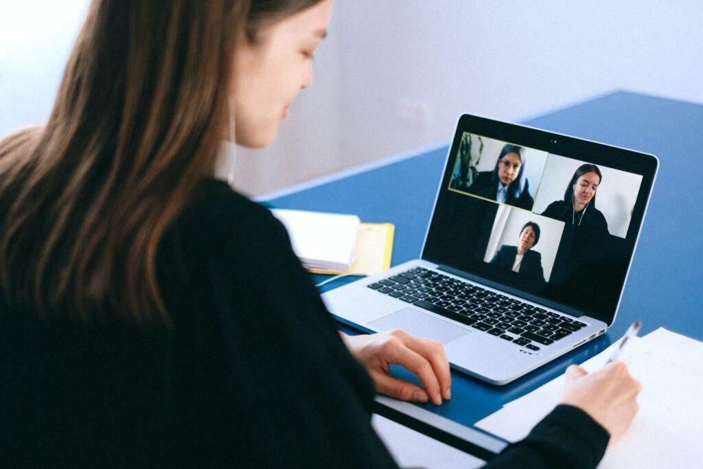 Una mujer que tiene una entrevista virtual con otras dos personas, en representación de un grupo de compañeros de trabajo que discuten sobre las empresas tecnológicas de Bolivia.