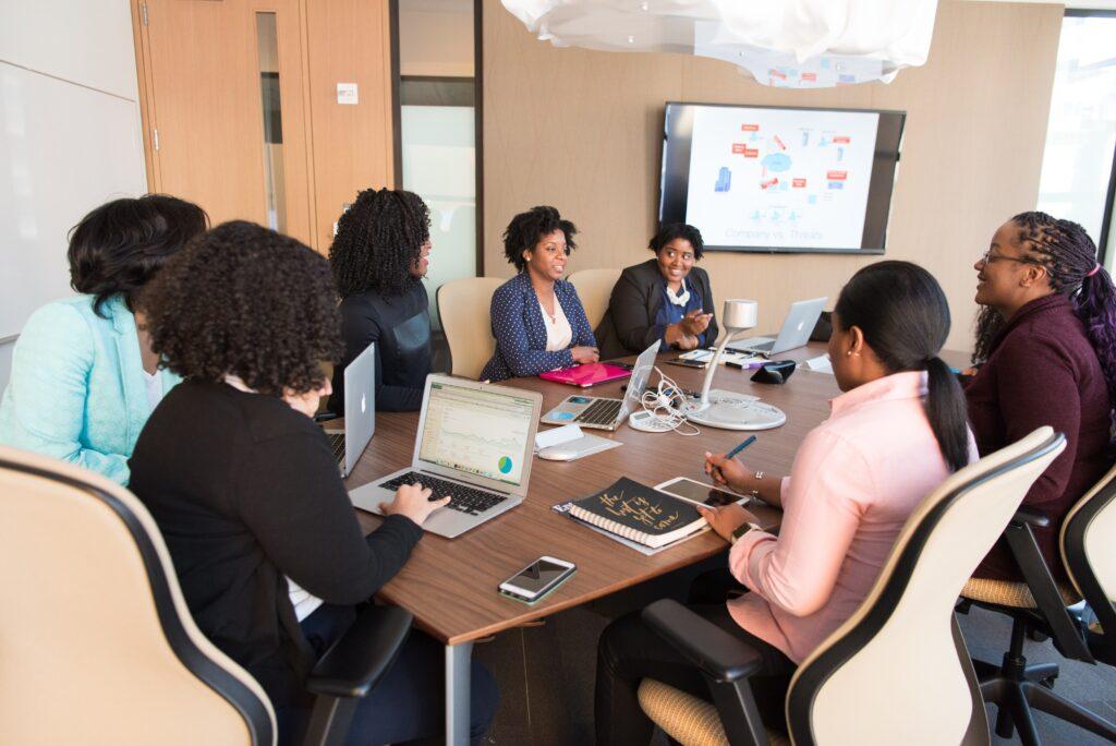 Siete mujeres en una reunión de negocios, en representación de agentes de formación de empresas discutiendo sobre la formación de LLC en Uruguay