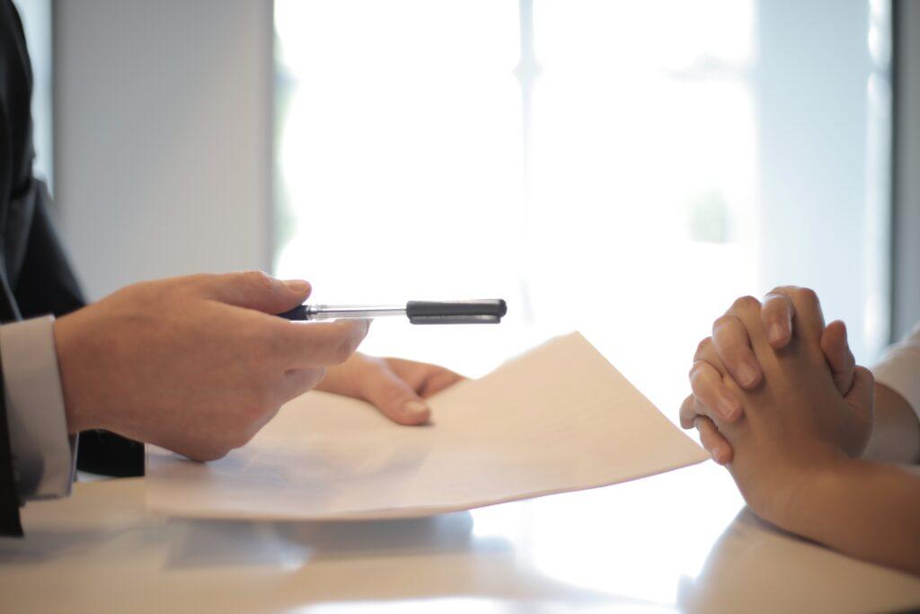 Two people handling paperwork, representing two people handling accounting records