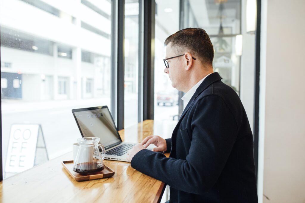 Empresario en una cafetería frente a una computadora, en representación de un abogado corporativo en República Dominicana.