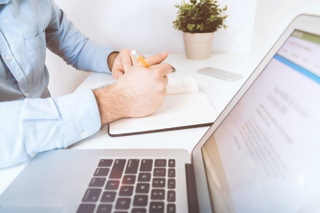 Hombre usando una computadora portátil y tomando notas en una agenda, representando a una persona que busca información sobre cómo registrar una subsidiaria en República Dominicana.