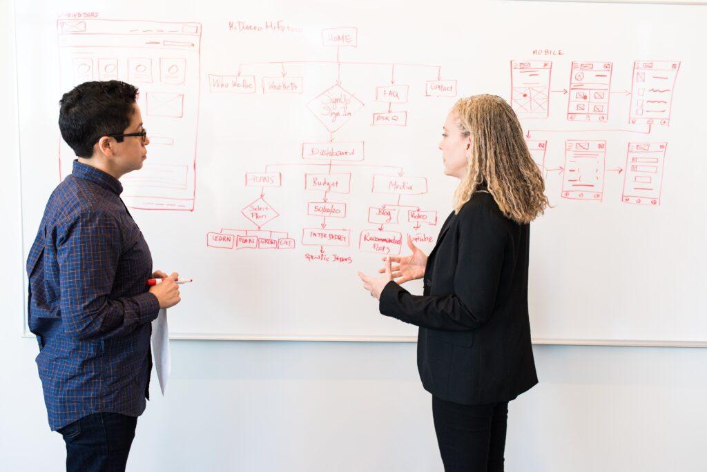 Dos personas que hacen anotaciones en un tablero, que representan a dos abogados de un proveedor de servicios legales corporativos.