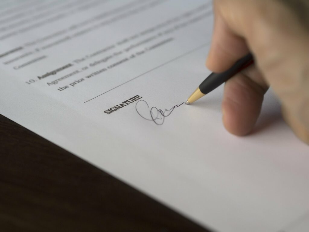 A stock image of someone signing a contract accompanying an article on employment law in Ecuador