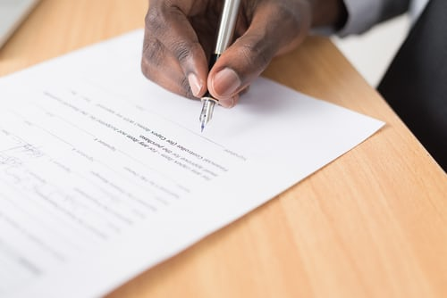 A stock image of someone signing paperwork, representing one of the four main types of contract under employment law in Brazil