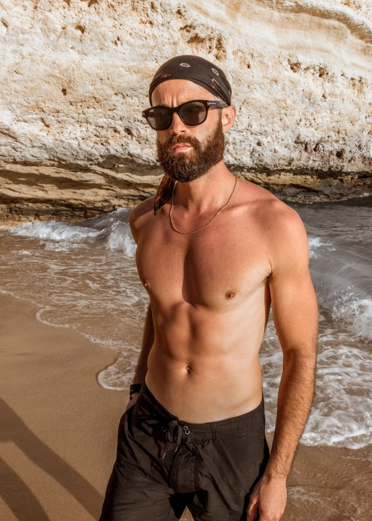 Michael Checkers wearing Onia swimtrunks in Lagos Portugal on the beach
