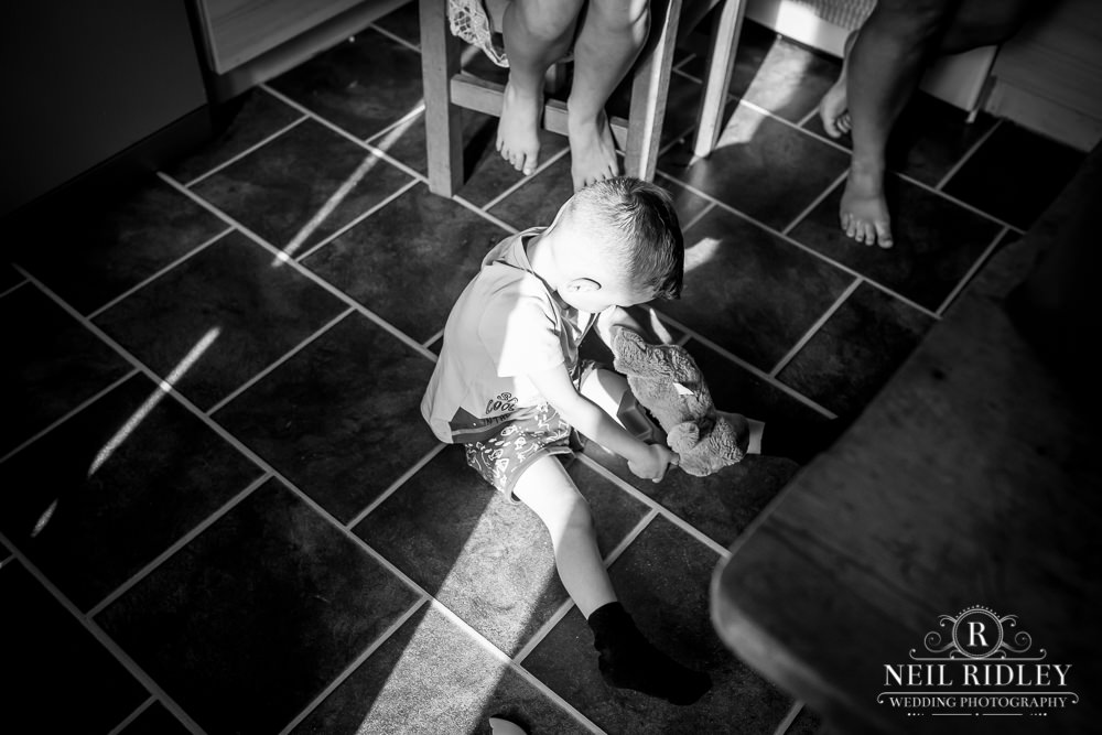 Manchester Wedding Photographer black and white image of small boy sat on kitchen floor.
