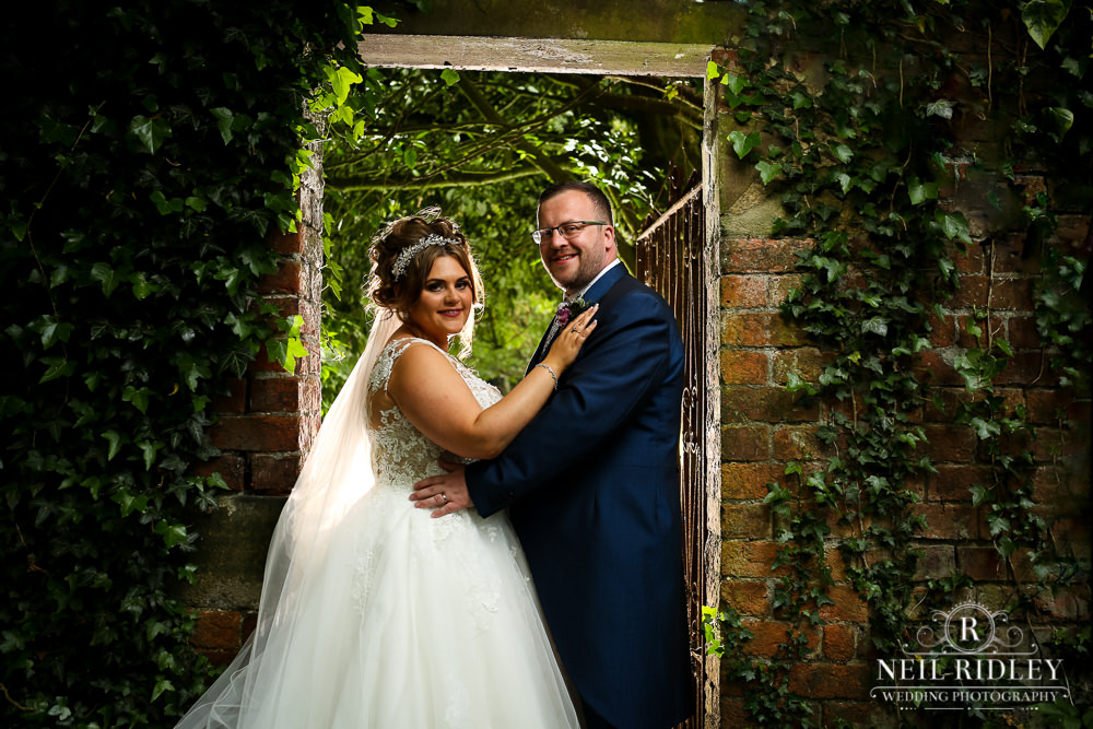 Bartle Hall Wedding Photographer Backlit portrait of the Bride and Groom in the garden archway