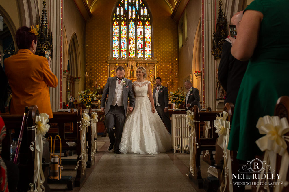 Manchester Wedding Photographer  Bride and Groom walking down the aisle
