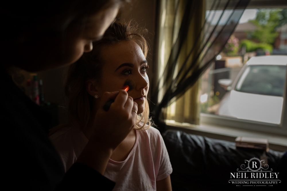 Manchester Wedding Photographer  bridesmaid having her make up applied by maker up artist during bridal prep