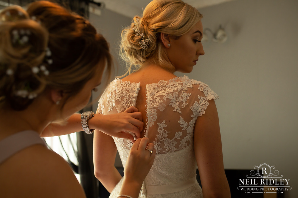 Manchester Wedding Photographer  rear shot of bride to be in her dress whilst having her buttons fastened